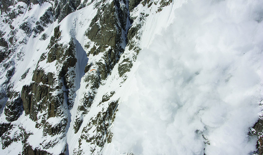 John Silvester is a speck against the huge face of Nanga Parbat as an avalanche explodes on the mountain. Photo: Olivier Laugero